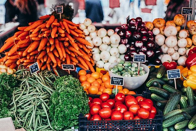Sur une étale de marché, on voit des fruits et légumes colorés et des ardoises annoncent le prix. / applis éco-responsable