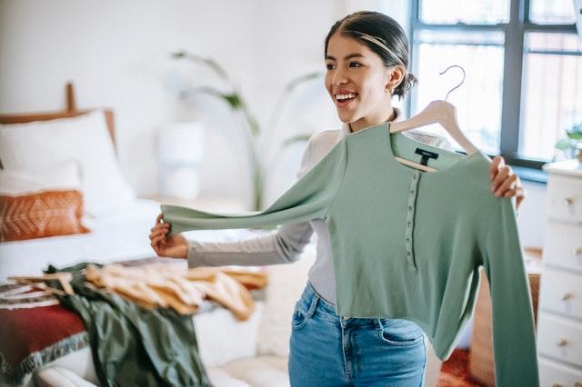 Une jeune femme range ses affaires et essaie une veste verte dans sa chambre / trier ses affaires pour la rentrée