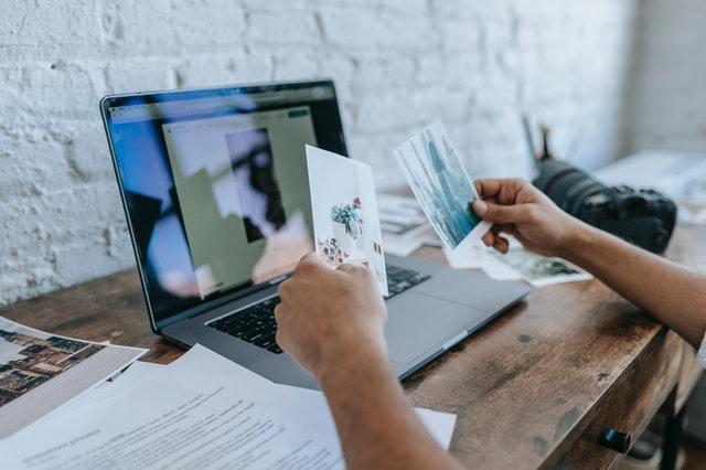 Un homme classe et range des papiers devant un ordinateur sur un bureau / trier ses affaires pour la rentrée