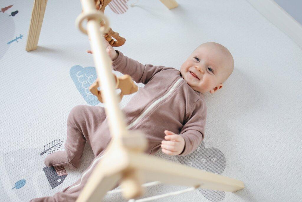 Un bébé sous un portique s'amuse en regardant ses jouets. / article bébé seconde main