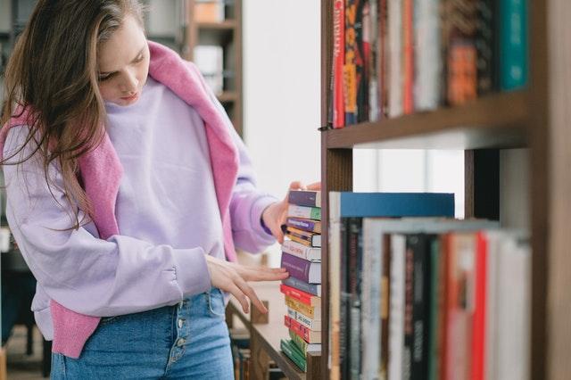 Une jeune femme cherche des livres dans une bibliothèque. / trier ses affaires pour la rentrée