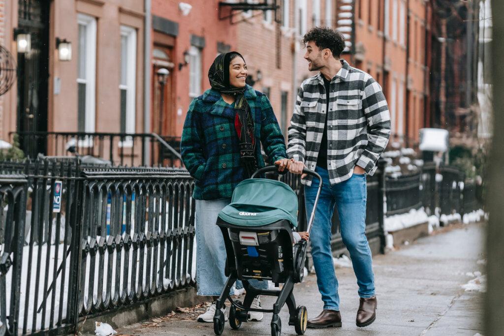 Une mère et un père promènent leur bébé en poussette dans la ville. Ils sourient et semblent heureux. / article bébé seconde main