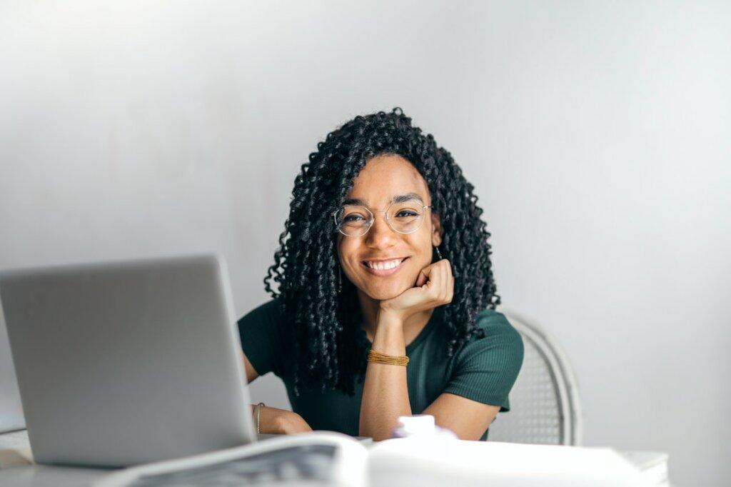 Une jeune femme à lunettes, souris devant un ordinateur, assise à un bureau / se meubler pas quand on est étudiant