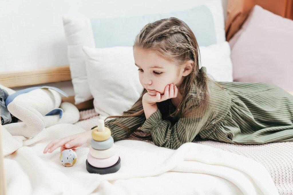 Une petite fille est allongée sur un canapé blanc et joue avec des jeux en bois.  / marques de jouets écologiques