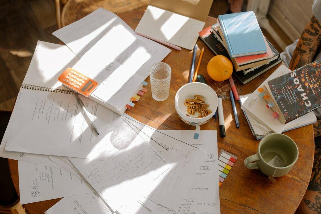 Sur une table ronde, des cahiers, livres et feuilles sont disposés de manière éparse, à côté de vaisselles et nourriture. / se meubler pas cher quand on est étudiant