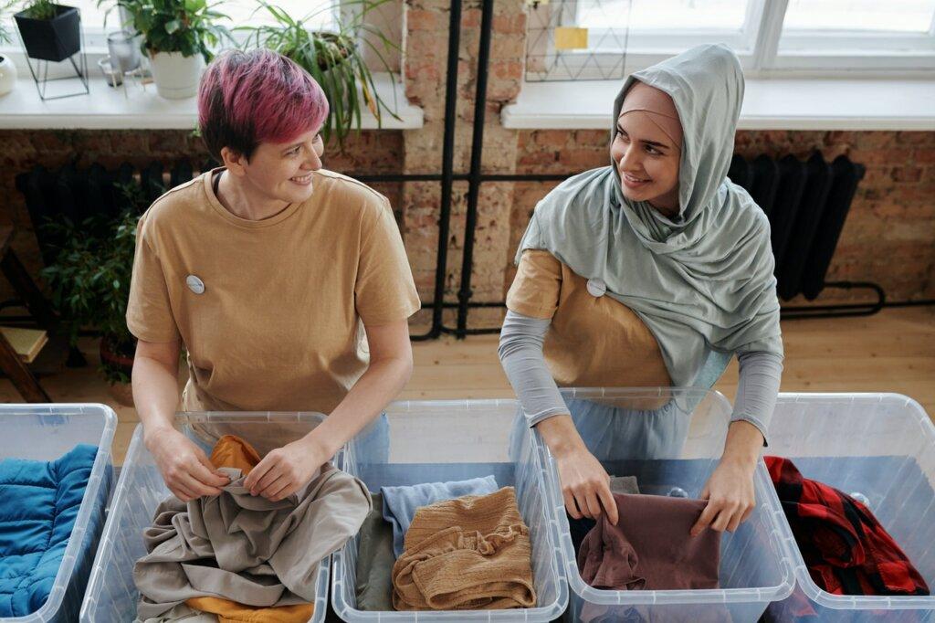Deux femmes rangent des vêtements dans des boites pour une association / conseils pour ranger son dressing