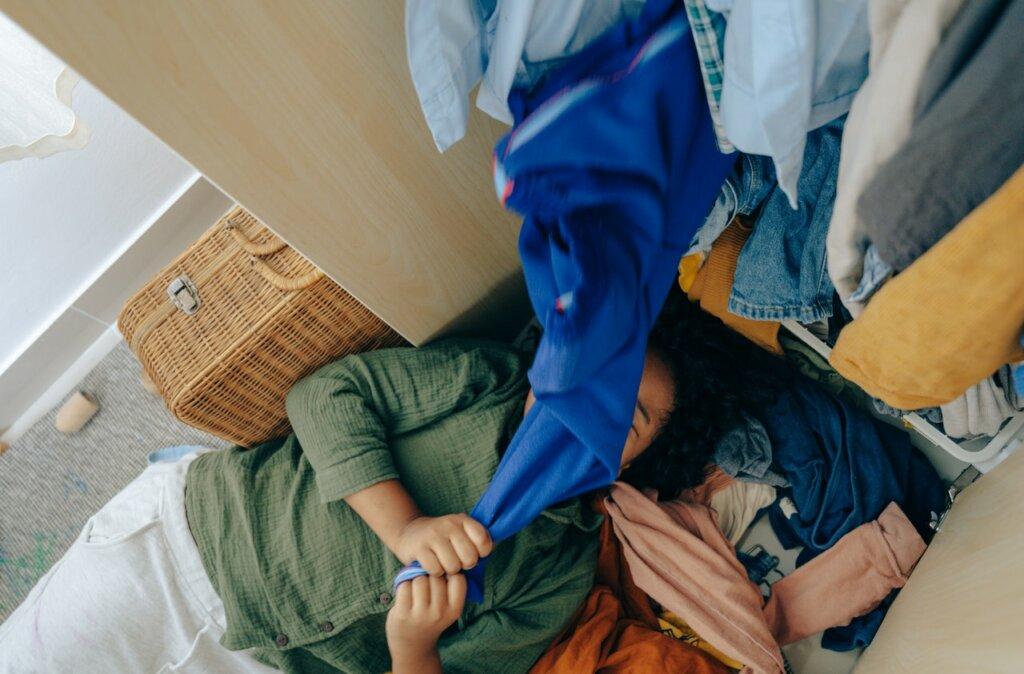 Une femme est ensevelie sous les vêtements de son armoire / conseils pour ranger son dressing