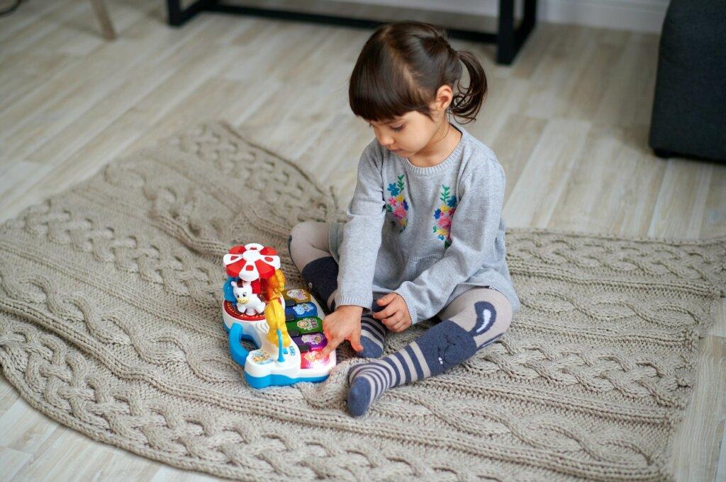 Une petite fille assise sur le sol avec une couverture, joue avec un piano musical en plastique. / marques de jouets écologiques
