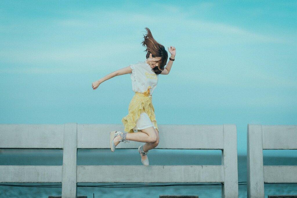 Une femme saute dans la rue, près d'un plan d'eauet devant une barrière en bois et sourit. / applis éco-responsable