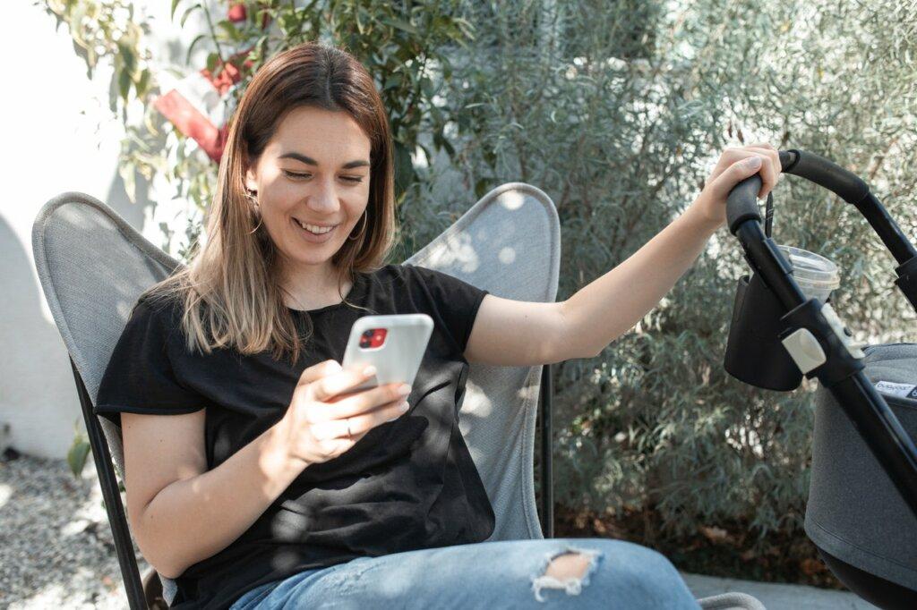En extérieur, une jeune femme souriante berce une poussette en regardant son smartphone. / applis éco-responsable