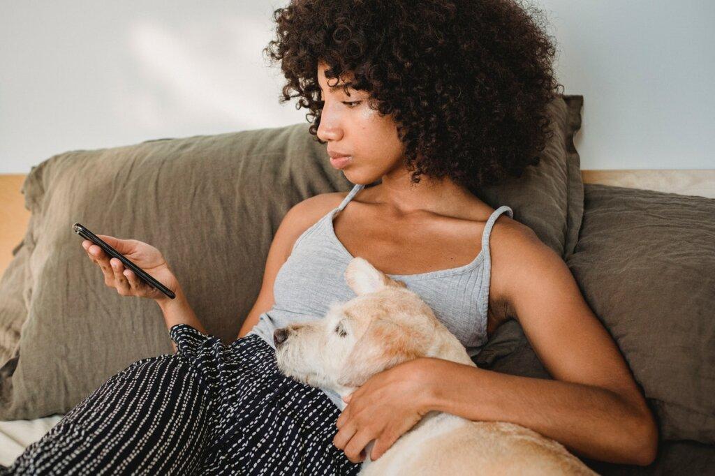 Une jeune femme utilise son smartphone assise sur son lit avec son chien / recycler ses vieux livres