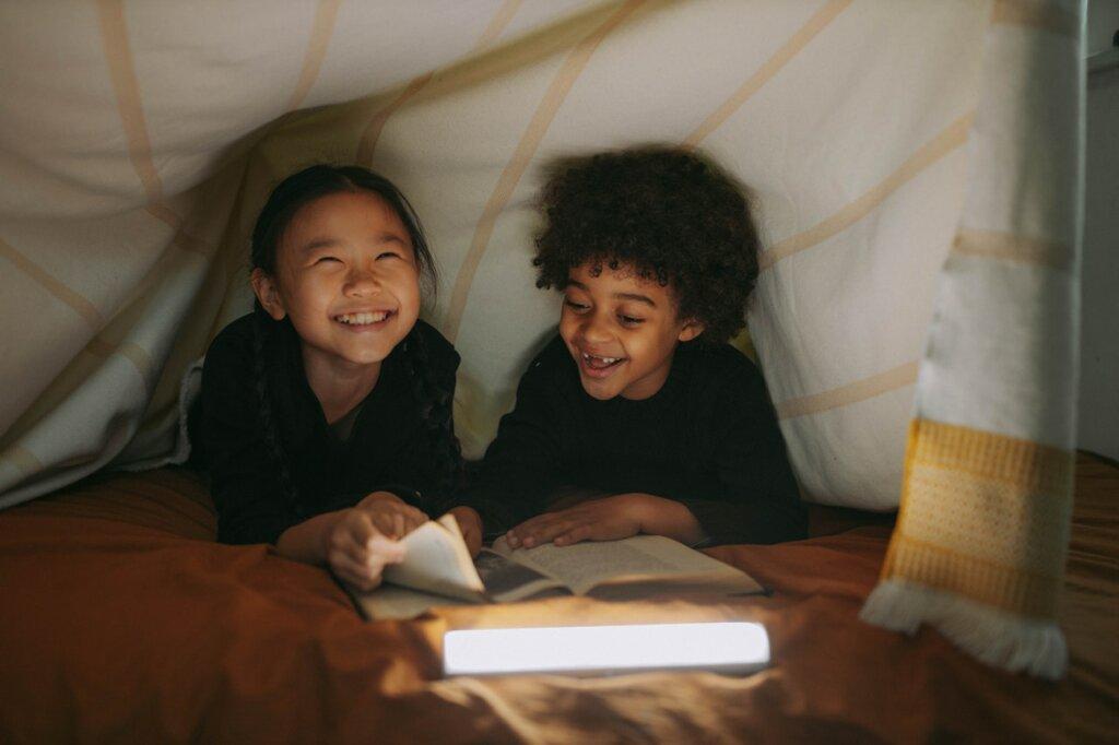 Une petite fille et un petit garçon sont souriants sous une tente, éclairée à la lampe de poche, ils regardent des livres. / recycler ses vieux livres